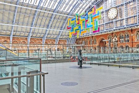 LONDON - JUNE 7. Standing in the restored and redeveloped St Pancras International rail station is a statue of Sir John Betjeman who saved the building from demolition; June 7, 2014 in London, UK.