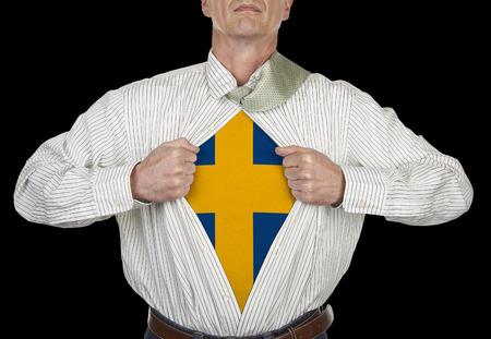 Businessman showing Sweden flag superhero suit underneath his shirt standing against black background