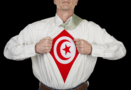 Businessman showing Tunisia flag superhero suit underneath his shirt standing against black background