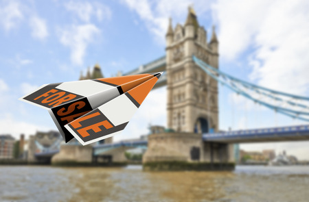 The Tower Bridge in London and Flying paper plane with the words for sale 免版税图像