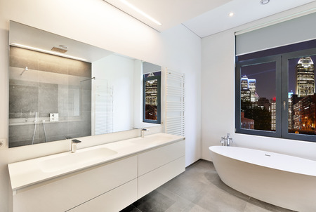 Bathtub in corian, Faucet and shower in tiled bathroom with windows towards night city lights