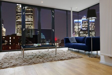 Modern living room with large windows and view on city panorama. There are path for windows