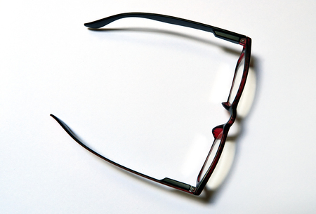 Elegant eyeglasses on white sheet with reflections and shadows, view from above Stock Photo