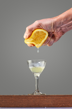 Male hand pressing a half lemon fruit