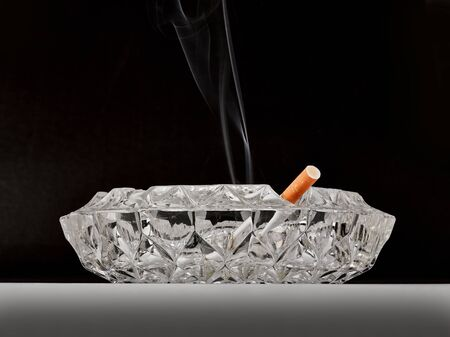 Ashtray with cigarette and smoke from front
