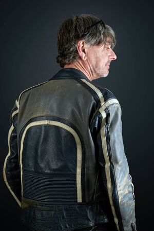 Portrait of a man with leather biker jacket on gradient background