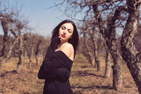 Brunette in a spring apple orchard