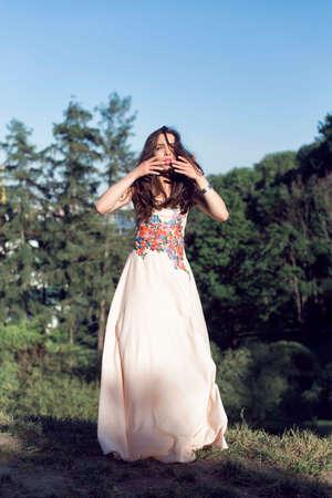 Girl in a long dress walking in the botanical garden