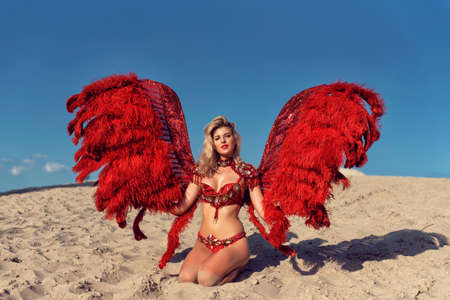Young blonde with red wings on the sand
