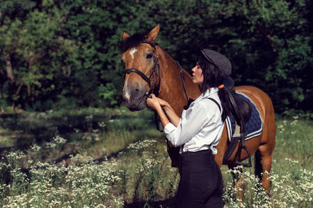 Summer walk of the girl with a brown horse Banque d'images