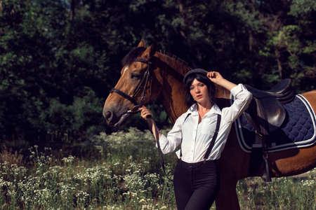Promenade d'été de la fille avec un cheval brun Banque d'images