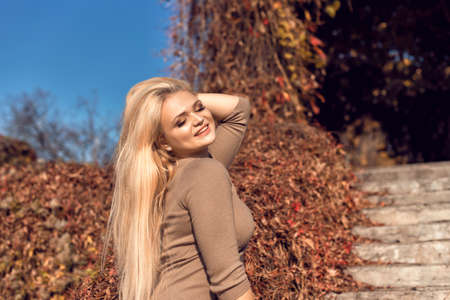 Autumn walk in the park with a cute blonde 스톡 콘텐츠