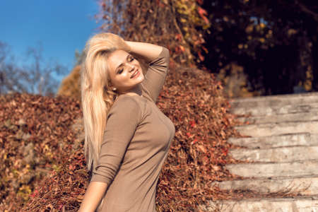 Autumn walk in the park with a cute blonde 스톡 콘텐츠 - 133463875