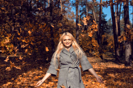 Autumn walk in the park with a cute blonde 스톡 콘텐츠 - 134018585