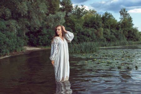 Girl in an embroidered dress on the lake