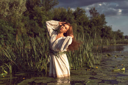 Girl in an embroidered dress on the lake Standard-Bild