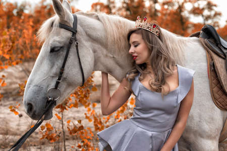 Young woman in the park with a horse