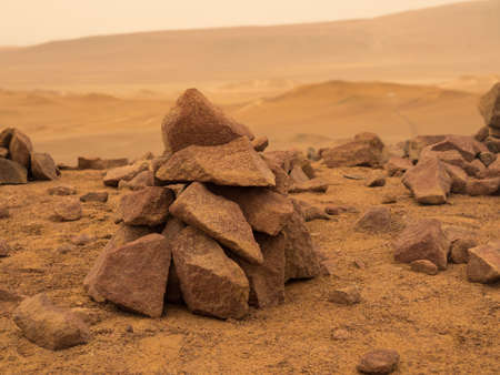 Piles of rocks in a deserted red terrestrial planet with thick atmosphere.