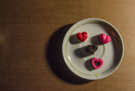 A Pink-Heart lovely face Chocolate on top of a plate, on the wood. Zdjęcie Seryjne