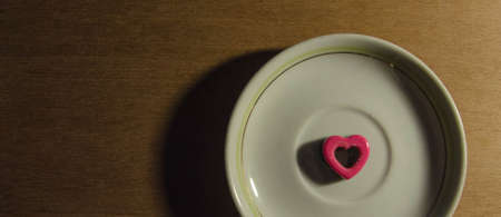 A Pink-Heart Chocolate on top of a plate, on the wood.
