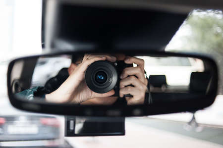 drivers seat: man holding a camera sits on drivers seat and Looks in the rear-view mirror Stock Photo