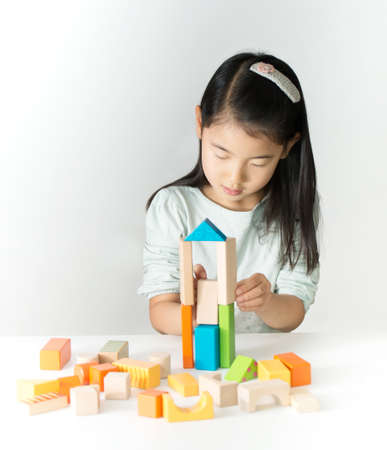 wood blocks: little Asian girl playing colorful wood blocks
