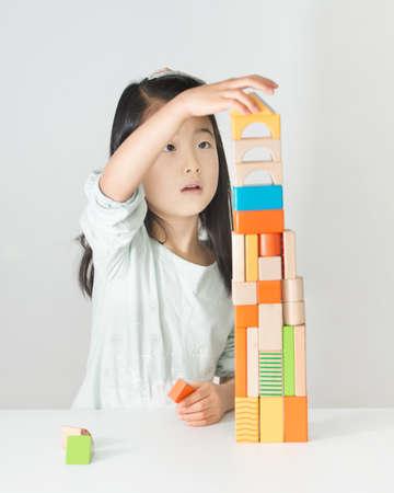 Kleinen asiatischen Mädchen spielt bunte Holzblöcke Standard-Bild - 50790652