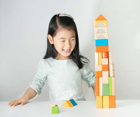 kleine Aziatische meisje spelen kleurrijke houten blokken