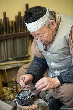 folk village: Seoul, South Korea - January 28, 2016: An artisan at the Korean folk Village in Yongin, Korea works his craft of weaving on Jan 28, 2016. Korea traditional copper pipe tobacco production craftsmen Editorial