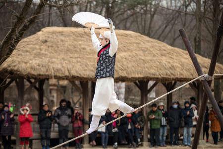 the acrobatics: Se�l, Corea del Sur - 28 de enero 2016: La acrobacia en la cuerda floja caminando en la aldea popular coreana el 28 de enero de 2016 Yongin, Corea del Sur. Villa folkl�rica coreana, es un tipo de museo vivo de atracci�n tur�stica. Editorial