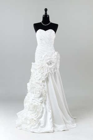 Moderne witte trouwjurk op een grijze achtergrond Stockfoto