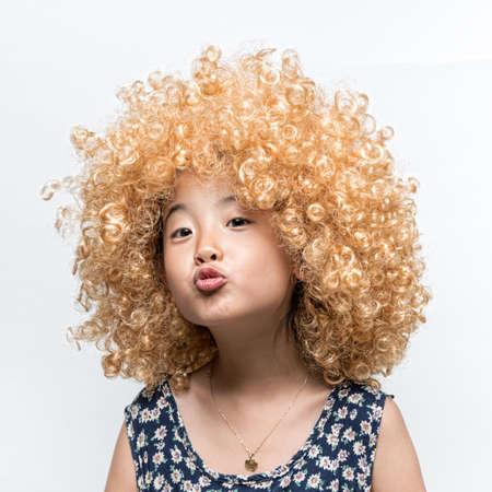 금발의 가발 및 재미 있은 표정을 끼고 아시아 소녀