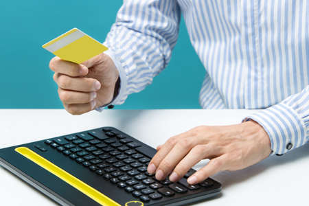 Man hands using keyboard and holding credit card with social media as Online shopping concept on blue background