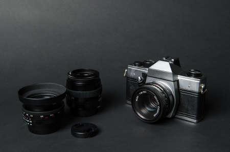 Old film camera and manual lens, black background Standard-Bild - 105003819