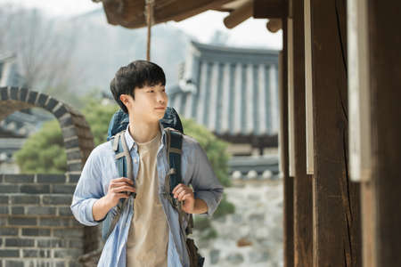 A young man doing a backpacking trip in a Korean traditional house. Standard-Bild - 99221635