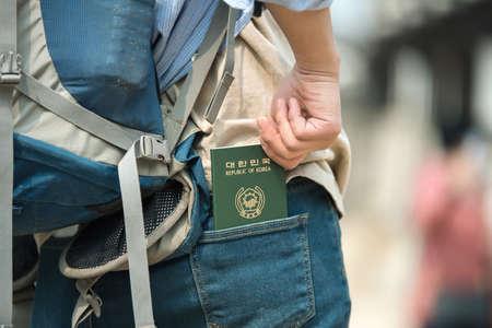 Travelers take their Korean passports out of their jeans back pockets. Zdjęcie Seryjne