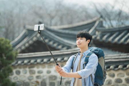 Ein junger Mann , der reist , um Korea , die Bilder mit seinem Smartphone zu machen Standard-Bild - 98880485