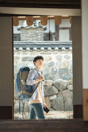 A young man doing a backpacking trip in a Korean traditional house. Standard-Bild - 99221637