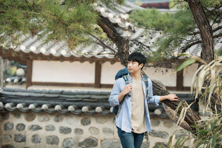A young man doing a backpacking trip in a Korean traditional house. Standard-Bild - 98907976