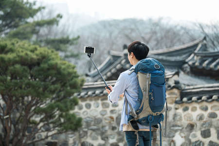 A young man who travels to Korea is taking pictures using his smartphone. Zdjęcie Seryjne