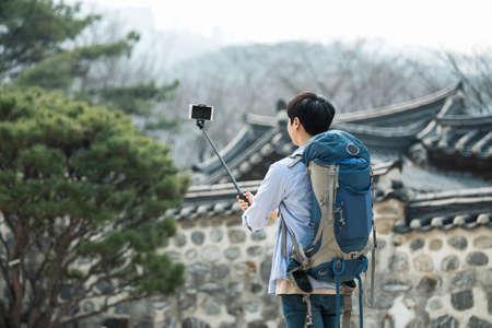 Ein junger Mann , der reist , um Korea , die Bilder mit seinem Smartphone zu machen Standard-Bild - 98880486