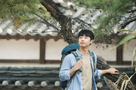 A young man doing a backpacking trip in a Korean traditional house. Standard-Bild - 99221695