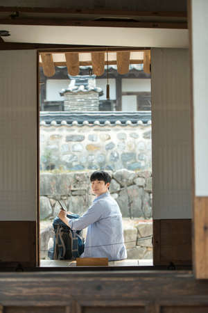 A young man doing a backpacking trip in a Korean traditional house. Standard-Bild - 99221696