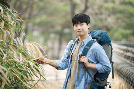 A young man doing a backpacking trip in a Korean traditional house. Standard-Bild - 99221697