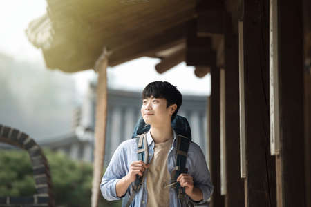 A young man doing a backpacking trip in a Korean traditional house. Standard-Bild - 99385150