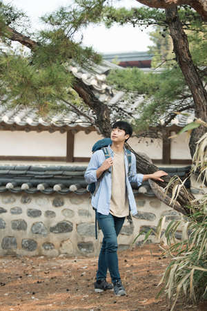 A young man doing a backpacking trip in a Korean traditional house. Standard-Bild - 98907998
