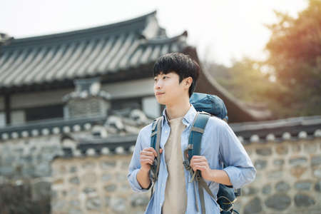 A young man doing a backpacking trip in a Korean traditional house. Standard-Bild - 98880491