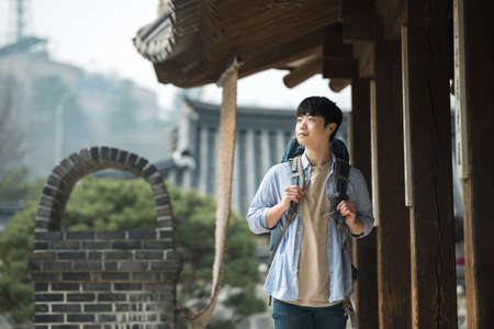 A young man doing a backpacking trip in a Korean traditional house. Standard-Bild - 98893762