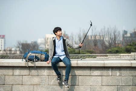 Ein junger Mann , der reist , um Korea , die Bilder mit seinem Smartphone zu machen Standard-Bild - 98892739