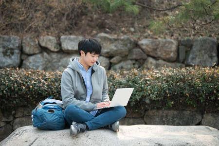 Asian man backpacking using laptop